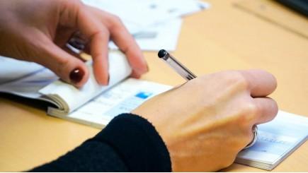 Een vrouwenhand schrijft met een pen in een boekje